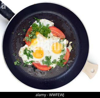 Fried eggs in pan with tomatoes and herbs. Clipping path - Stock Photo
