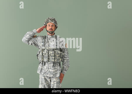 Saluting soldier on color background - Stock Photo