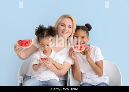Happy woman and her little African-American daughters eating watermelon on color background - Stock Photo
