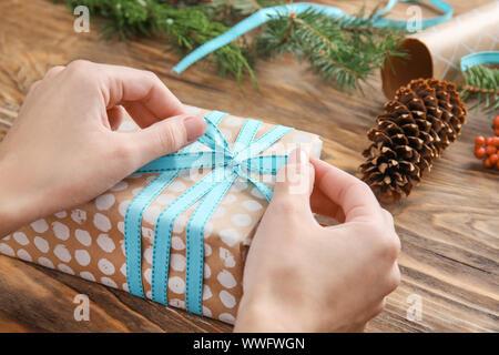Woman tying bow on Christmas gift box at table, closeup - Stock Photo