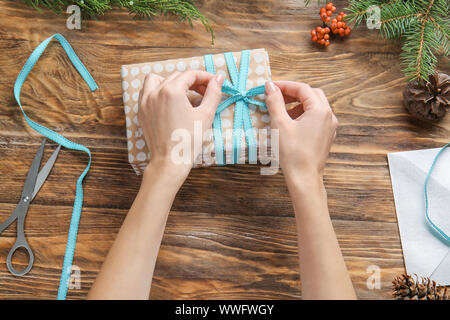 Woman tying bow on Christmas gift box at table - Stock Photo