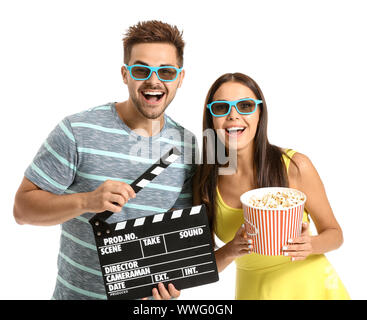 Young couple with popcorn and movie clapper on white background - Stock Photo