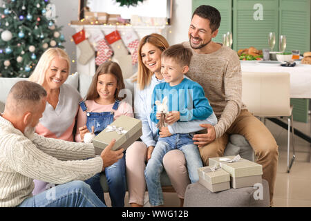 Little boy receiving Christmas gift from his grandfather at home - Stock Photo