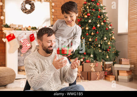Little boy greeting his father on Christmas eve - Stock Photo
