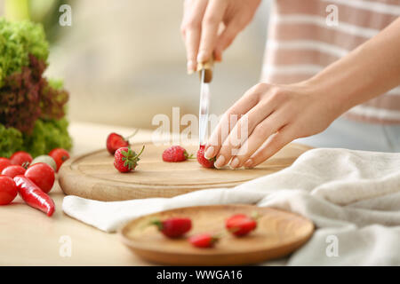 Woman cutting fresh strawberry at table