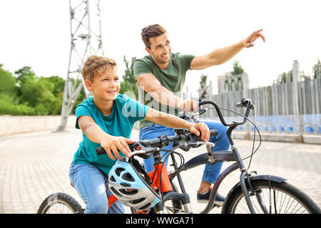 Happy father and son riding bicycles outdoors - Stock Photo
