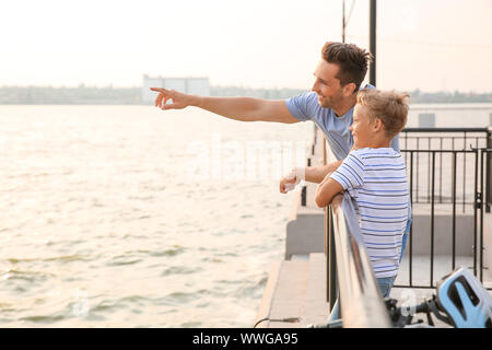 Father and his little son with bicycle near river - Stock Photo