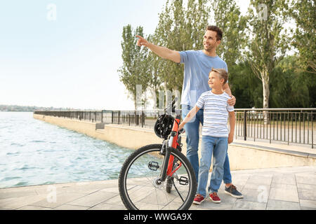 Father and his little son with bicycle outdoors - Stock Photo