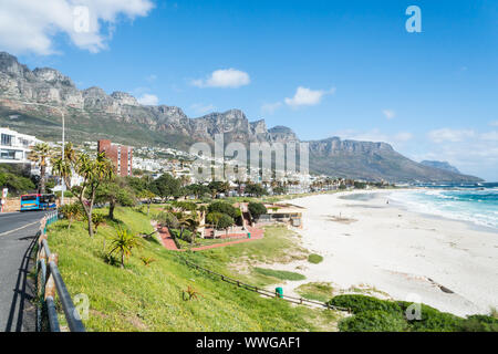 scenic view onto the upmarket suburb of Camps Bay in Cape Town, South Africa with its white sandy blue flag beach and the Twelve Apostle mountains - Stock Photo