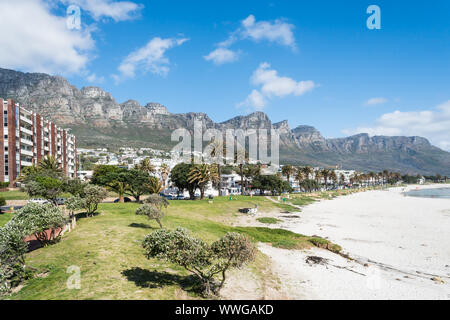 Camps Bay white sandy blue flag beach in Cape Town, South Africa scenic view onto the upmarket suburb with Twelve Apostle mountains in the background - Stock Photo