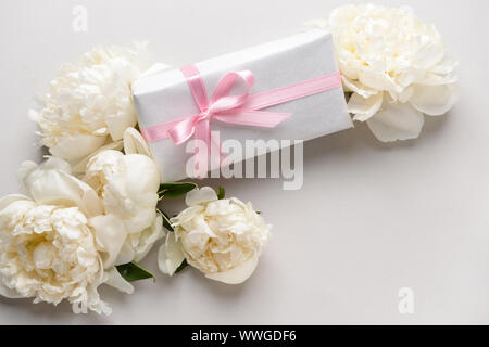 Gift box and beautiful flowers on light background