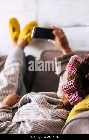 Relaxed young caucasian woman at home use smartphone lay down onthe sofa with home dress and curlers for hair- people and beauty carefree concept - Stock Photo