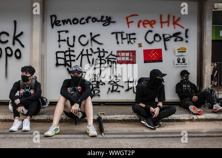 Hong Kong. 15th Sep, 2019. Protesters sat in front of graffitis at a tram stop in Causeway Bay during a pro-democracy march. Protesters continue to demonstrate across Hong Kong for the 15th consecutive week. After marching for few hours from Causeway Bay towards Admiralty, clashes between protesters and riot police occurred in different parts of the island. Credit: SOPA Images Limited/Alamy Live News - Stock Photo