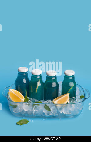 Blue isotonic drink with fresh lemons and ice cubes - Stock Photo
