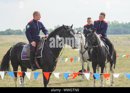 Samara, Russia - August 22, 2019: Young Cossacks in traditional costumes on horseback - Stock Photo