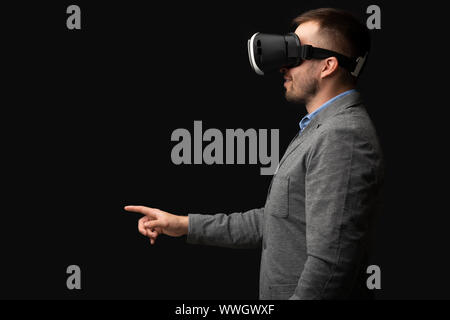 Caucasian businessman in VR headset pointing to virtual object - Stock Photo