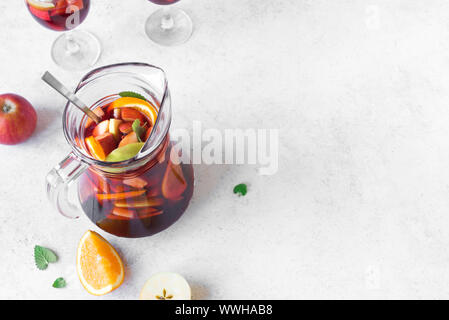 Red wine sangria or punch with fruits and ice in pitcher. Homemade refreshing fruit sangria on white background, copy space. - Stock Photo