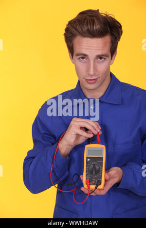 Electrician using a multimeter - Stock Photo