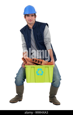 Man recycling bricks - Stock Photo