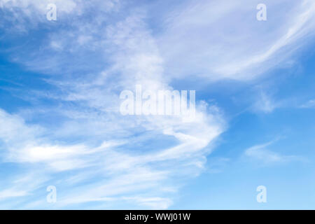 Scenic fluffy cirrus and stratus clouds in the stratosphere. Light spindrift clouds high in the blue summer sky. Different cloud types and climate. - Stock Photo