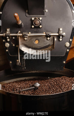 The freshly roasted coffee beans from a large old coffee roaster being stirred in the cooling cylinder. - Stock Photo