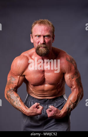 Middle aged Caucasian body builder man flexing muscles showing torso pecs, biceps and veins, isolated. - Stock Photo