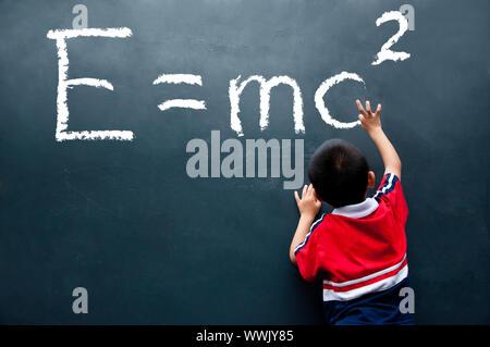 boy drawing E=mc2 on the wall - Stock Photo
