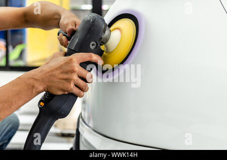 Man working for polishing, coating cars. polishing of the car will help eliminate contaminants on the surface of the car.Waxing the car surface will c - Stock Photo