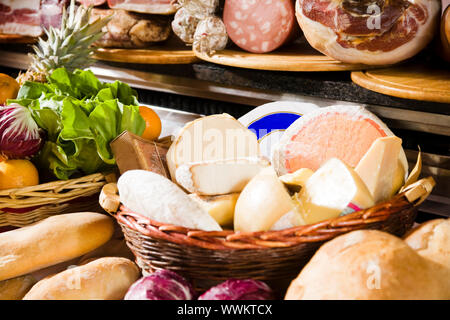 Assortment of cheeses in basket, meats and breads - Stock Photo