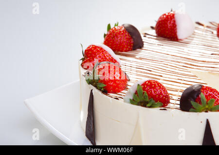 Cheesecake with chocolate and strawberries clousr-uo on the white plate - Stock Photo