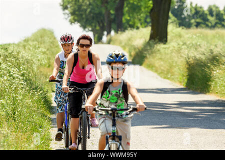 Mother with two sons on bicycle trip - Stock Photo