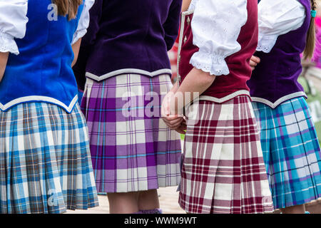 Young highland dancing girls wearing colourful tartan kilts at the Peebles highland games. Peebles, Scottish borders, Scotland - Stock Photo