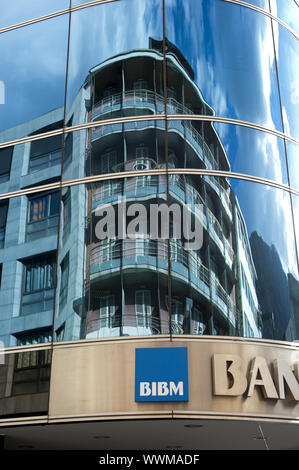 Reflections in the glass façade of the Banc Internacional d'Andorra - Banca Mora (BIBM) - Stock Photo