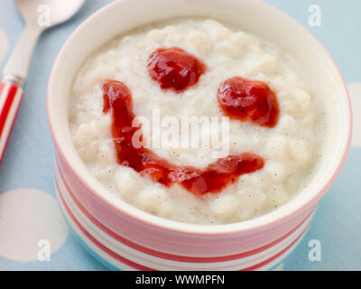 Bowl of Creamed Rice Pudding with a Strawberry Jam Face - Stock Photo