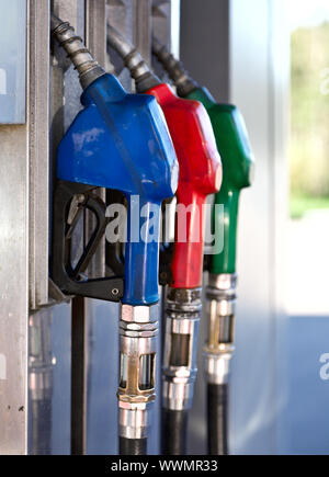 Three colorful pump nozzles at the gas station - Stock Photo