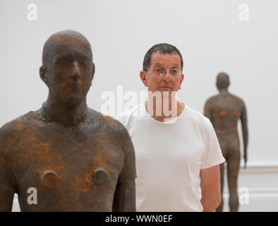 Royal Academy of Arts, London, UK. 16th September 2019. Internationally acclaimed British sculptor Antony Gormley (b. 1950) photographed in his major new exhibition at the RA. The exhibition is his most significant solo show in the UK for over a decade, bringing together both existing and especially conceived news works, from drawings and sculptures to experiential environments across all 13 rooms at the RA. Image: Antony Gormley with his installation 'Lost Horizon 1', 24 life-size cast iron figures set on the walls, floor and ceiling. Credit: Malcolm Park/Alamy Live News. - Stock Photo