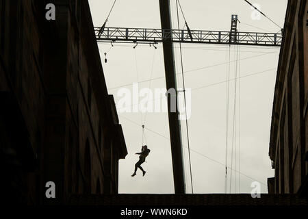 Edinburgh    September  16 2019;  A Fast and Furious 9 stuntman between the National Museum of Scotland and Edinburgh University.  The stuntman is attached to cables and appears to jump between the buildings.credit steven scott taylor / alamy live news - Stock Photo
