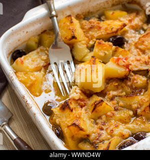 Fish with potatoes  and olives cooked in oven in small casserole - Stock Photo