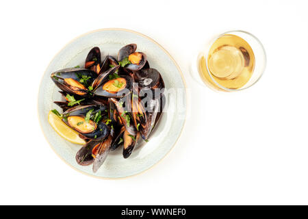 Marinara mussels, moules mariniere, shot from the top on a white background with a glass of wine and copy space - Stock Photo