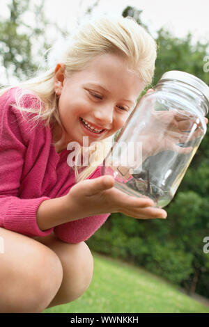 Girl Looking at Grasshopper in Jar - Stock Photo