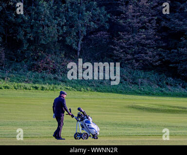 A golfer walking with golf trolley on the Glen Golf Course, North Berwick, East Lothian, Scotland, UK. - Stock Photo
