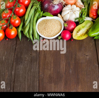 CousCous in a bowl and fresh vegetables on wood - Stock Photo