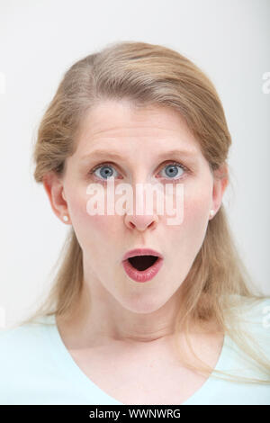 Pretty in look of surprise or amazment with her mouth open - Stock Photo