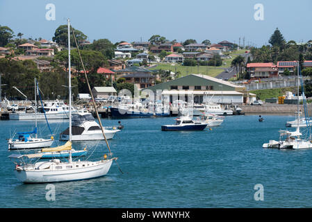 Large fishing trawlers and smaller recreational boats are moored in the harbour and at the marina in front of the Ulladulla Fisherman Co-op building. - Stock Photo