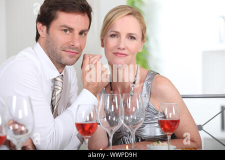 Couple sat at table enjoying intimate meal - Stock Photo
