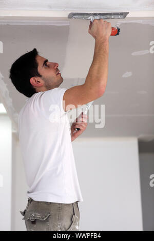 Man plastering ceiling - Stock Photo