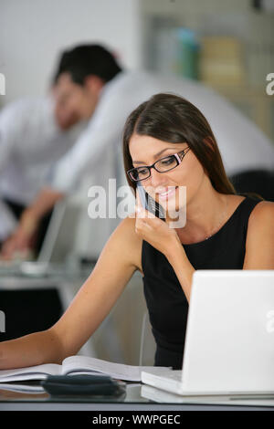 Brunette sat at desk working - Stock Photo