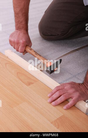 handyman laying floorboards - Stock Photo