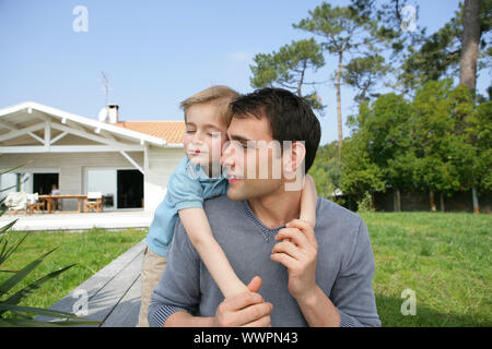 Little girl getting a piggy-back from father - Stock Photo