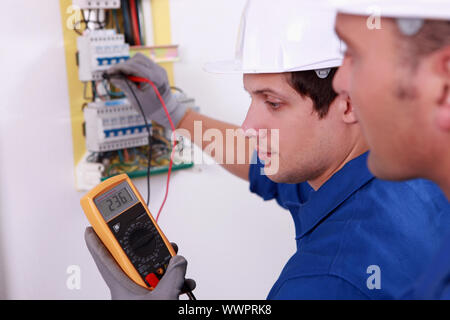 Two technical engineers checking electrical equipment - Stock Photo